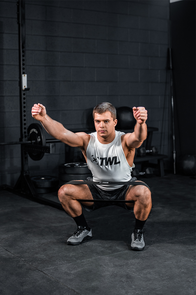 athlete doing banded air squat
