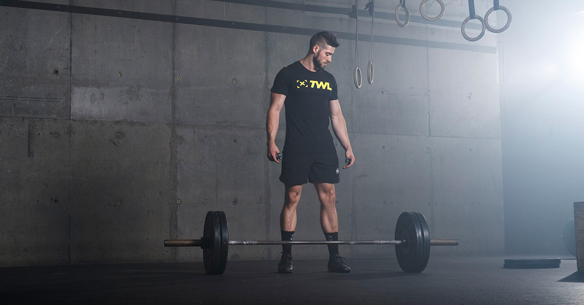 athlete standing over barbell