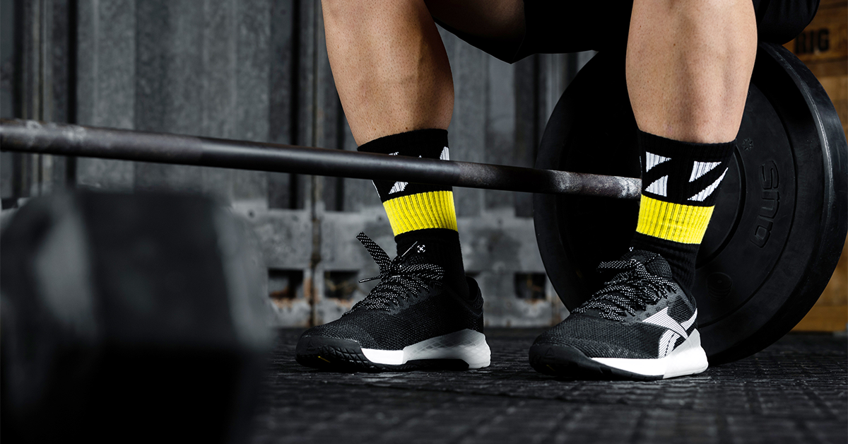 male athlete sitting next to barbell