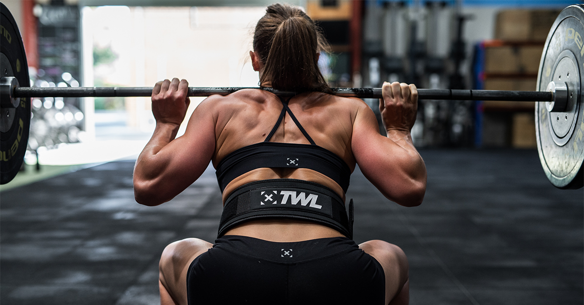 female athlete with barbell on back