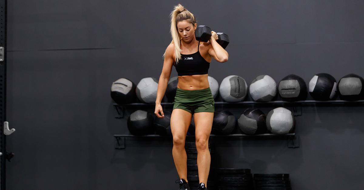 female athlete holding dumbbell on shoulder