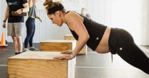 pregnant woman doing push-ups on plyo box