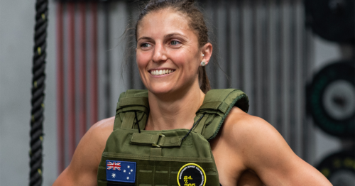 smiling woman running with a weighted vest