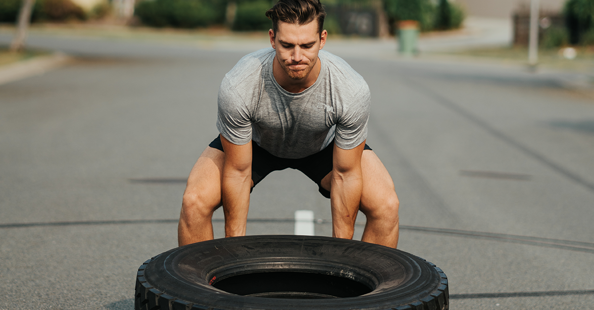male athlete flipping tire