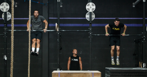 two male athletes doing pull-ups