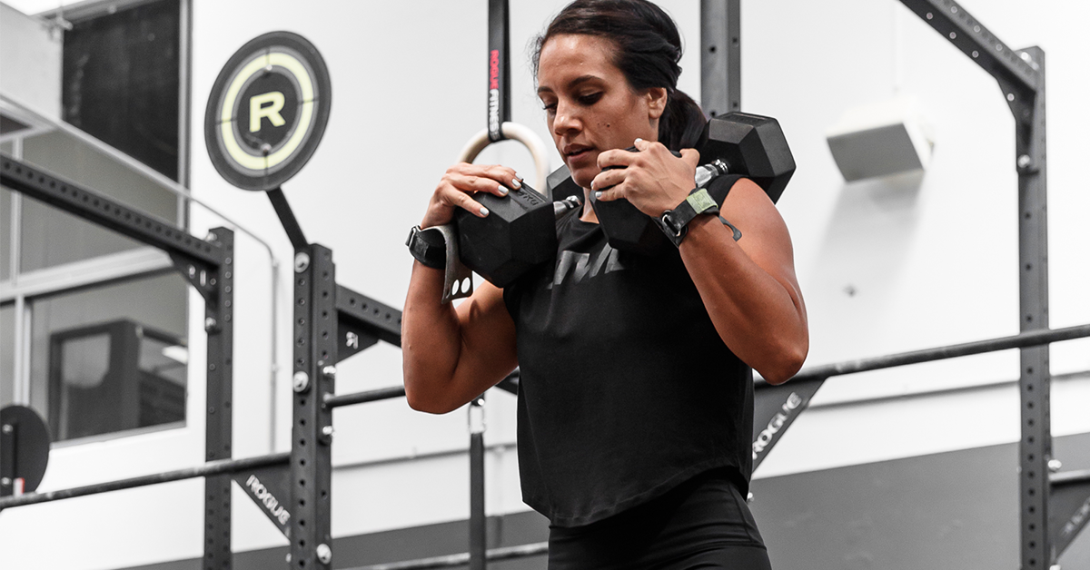 female athlete with dumbbells on shoulders