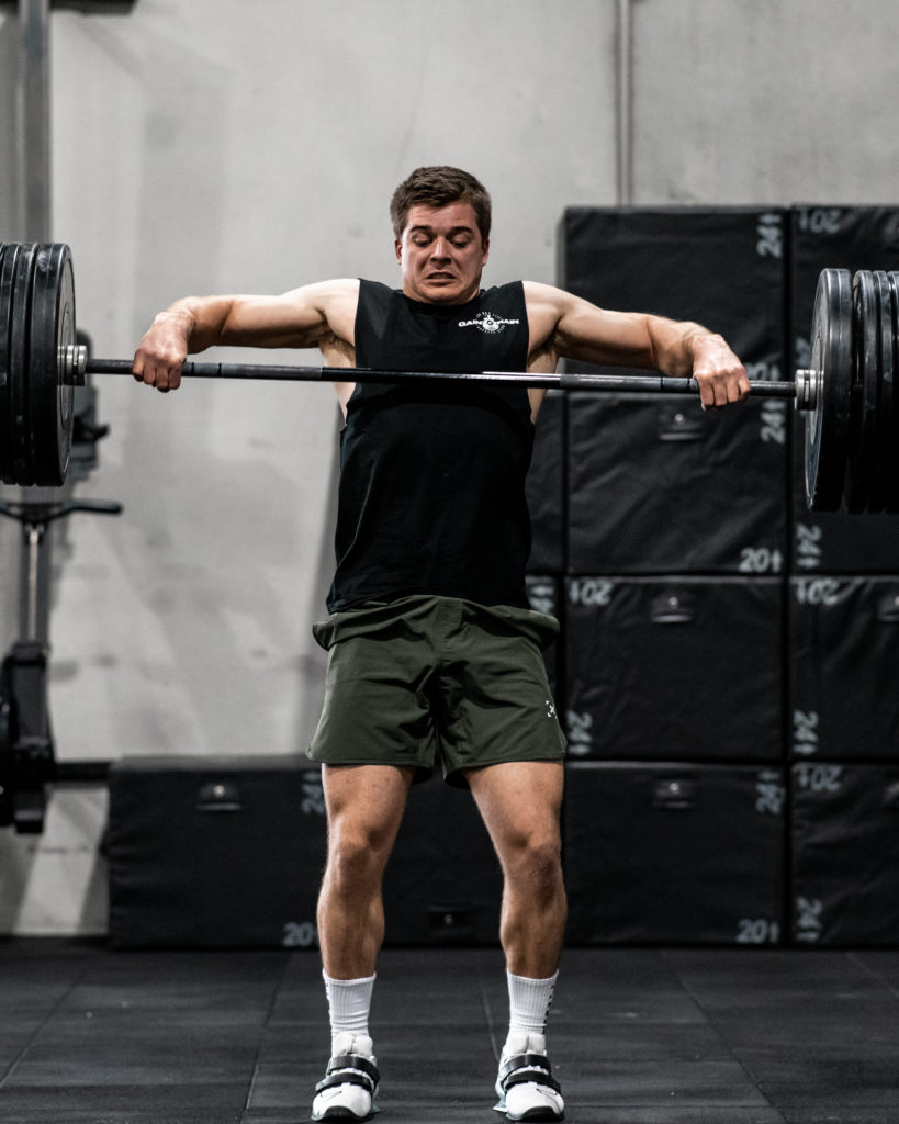 male athlete doing high pull in olympic weightlifting shoes