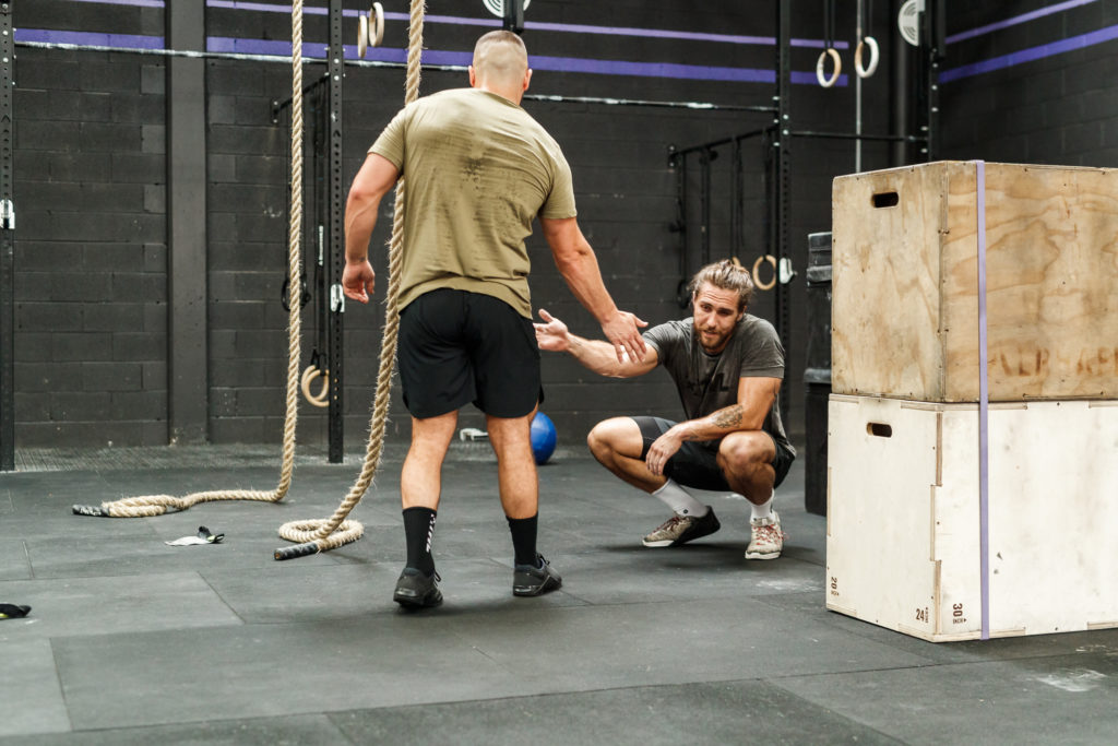 two male athletes high-fiving and enjoying the mental health benefits of exercise