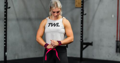 female athlete putting on wrist wraps
